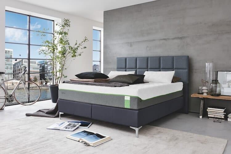 Das Bild zeigt ein marinefarbenes Bett der Marke Tempur, aus dem Sortiment von Bischoff Betten