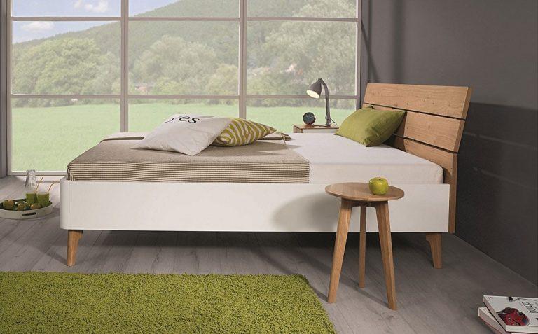 Auf dem Bild ist ein Holz Bett der Marke Reichert Möbelwerkstätte abgebildet