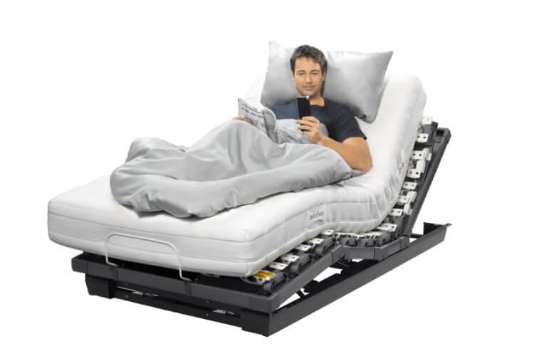 Das Bild zeigt ein Mann der auf einem Lattoflex Bett liest